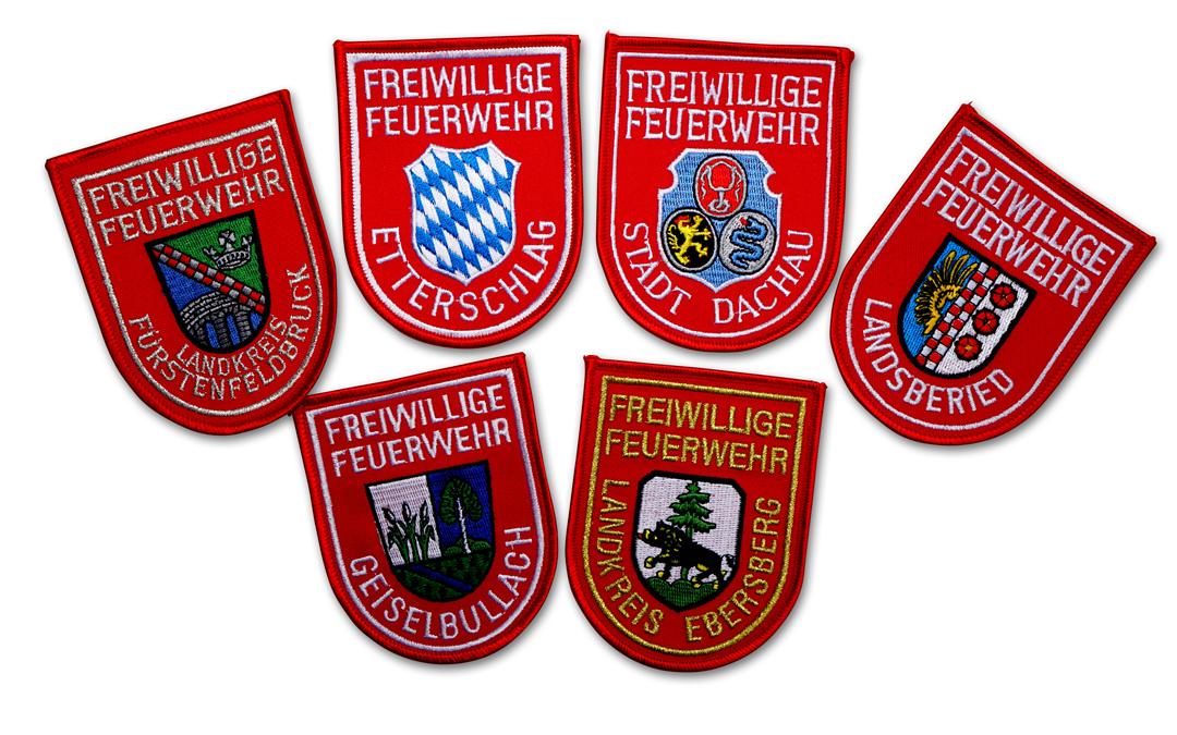 Fein gesticktes Armabzeichen mit weißer Schrift auf rotem Grund. Mit Text Freiwillige Feuerwehr und dem jeweiligen Ortsnamen. In der Mitte ist die Abbildung des Ortswappens oder ein Rautenwappen, je nach Wunsch