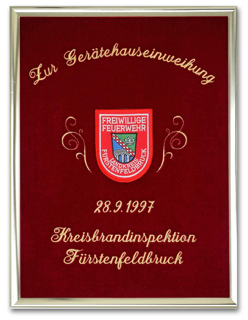 Gestickte Ehrentafel zur Gerätehauseinweihung. Schrift in Glanzgold gestickt. Als Motiv ist ein original Feuerwehr-Ärmelabzeichen aufgenäht.